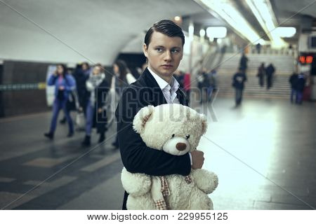 Sad Young Man In A Subway Station. He Holds A Toy Bear In His Hands
