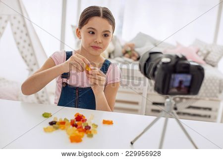 Love Candies. Upbeat Nice Pre-teen Girl Sitting At The Table In Front Of A Pile Of Gummy Bears And T