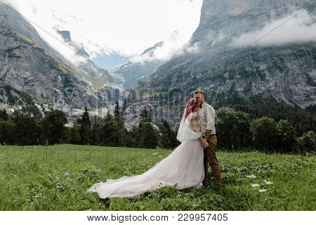 Bridal Couple Hugging On Green Mountain Meadow With Clouds In Alps