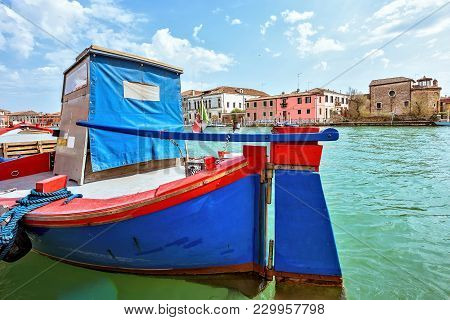 Daylight View To Vibrant Colorful Blue And Red Boat Parked In Venetian Lagoon
