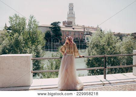 Young Elegant Woman In Glamorous Dress Posing At River In Verona, Italy