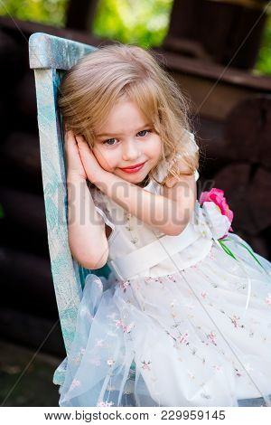 Cute Little Baby Girl In Beautiful White Dress Sitting On A Stump Chair At Playground In Recreation
