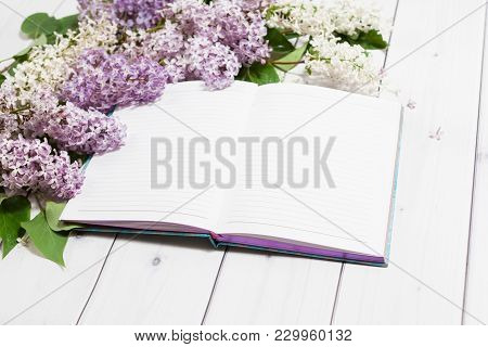 Beautiful White And Violet Lilac Flowers With Opened Note-book Lying On The White Wooden Background,
