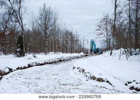Excavator By A Road Construction Workplace In Winter Season