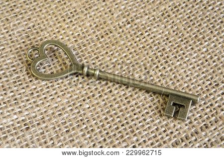 Antiquarian Bronze Key On Vintage Burlap. Material - Bronze. Decor. Indoors. Horizontal Format. Colo