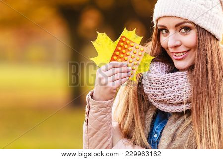 Woman In Autumn Park Holding Vitamins Medicines Showing How To Deal With Seasonal Autumnal Fever And