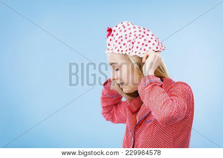 Young Woman Wearing Cute Pink Pajamas Putting Bathing Cap On Her Head.