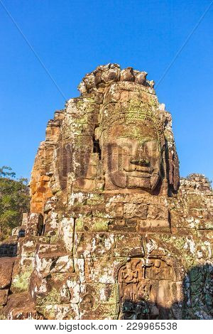 Face Of Lokesvara, One Of 200 At Bayon Temple Of Angkor Thom City Of Ancient Khmer Empire. Tourist T