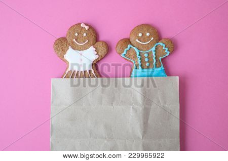 Homemade Gingerbread Man On Pink Background. Boy And Girl Peer Out Of The Package. Concept Of Gift.