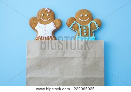Christmas Gingerbread Mans On Blue Background. Boy And Girl Peer Out Of The Package. Concept Of New