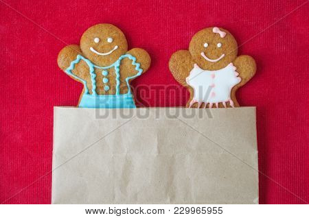 Christmas Gingerbread Mans On Red Velvet Background. Boy And Girl Peer Out Of The Package. Concept O