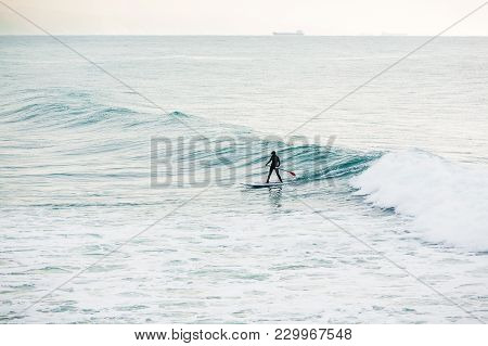 Surfer On Sup Board On Ocean Waves. Stand Up Paddle Boarding In Ocean