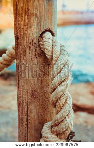 Detail Of Rope Railing Of Beach Walkway, Old Wooden Pole, Blue Sea Sand In The Background, Seaside V
