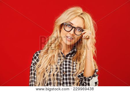 Attractive And Beautiful Blond Woman With Eyeglasses Holds Frame On A Red Background. Stylish Soluti