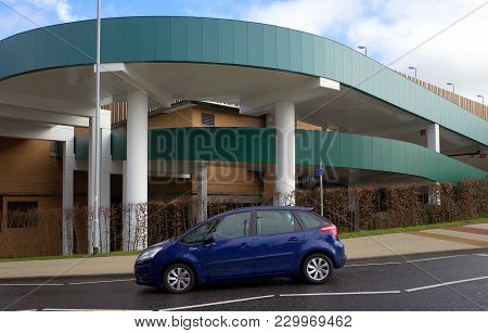 Bracknell, England - March 04, 2018: A Car Drives By The Concrete Ramp Entrance To One Of The Multi