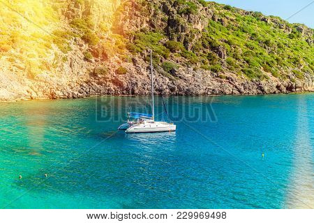 View Of The Sea Bay And A Sailing Catamaran Near A Steep Coast Of The Island Of Crete, Greece