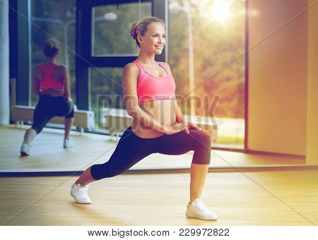 fitness, sport, training, gym and lifestyle concept - smiling woman stretching leg in gym