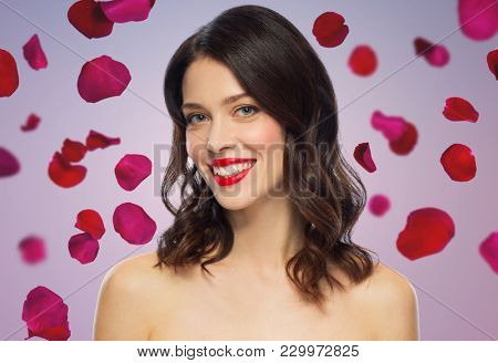 beauty, make up and people concept - happy smiling young woman with red lipstick over rose petals on background