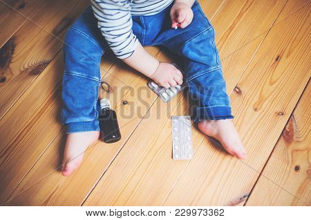 Unrecognizable Little Toddler Playing With Pills. Domestic Accident. Dangerous Situation At Home. To