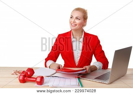 Beautiful Fitness Trainer Sitting At Table And Making Training Plan For Athletes