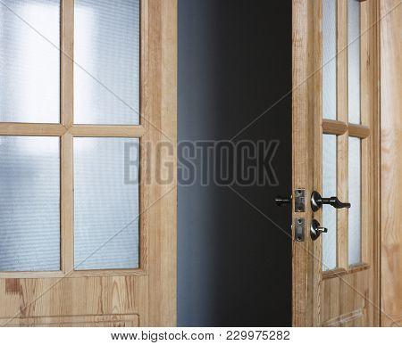 Slightly Slightly Open Wooden Door Leading To A Dark Corridor