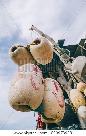 Blurred And Selective Focus Image Of Hanging White Dirty Fish Net Buoy And Kettle, Tied Together Wit