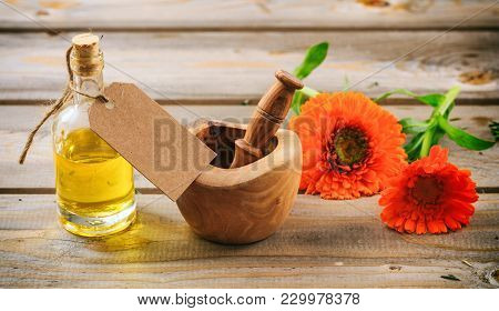 Calendula Essential Oil And Fresh Blooming Twig In A Mortar, Wooden Table, Blank Tag, Copy Space