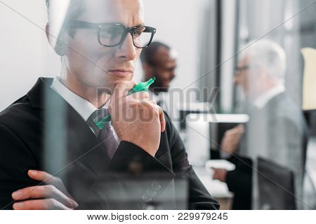 Selective Focus Of Focused Businessman Looking At Sticky Notes While Multicultural Colleagues Having