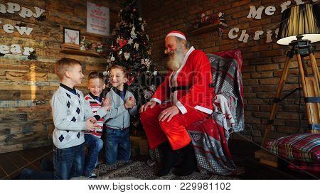 Three Brothers Kneeling In Front Of Santa, Laughing And Rejoicing And Asking To Tell Story About Lit