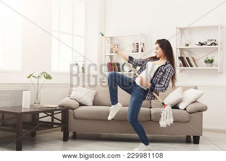 Happy Woman Cleaning Home, Playing On Mop Like On Guitar And Having Fun, Copy Space. Housework, Chor