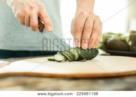 Helpful For Everybody. Green Cucumber Being On The Table Under The Knife Which Man Holding In His Ha