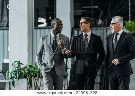 Smiling Multiracial Businessmen Having Conversation While Walking In Office
