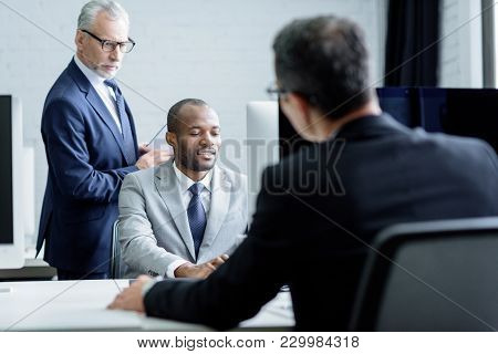Partial View Of Multicultural Businessmen Working Together In Office