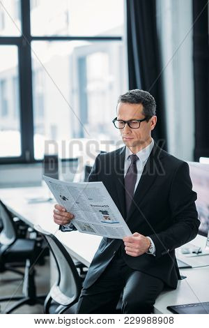 Portrait Of Focused Businessman Reading Newspaper In Office