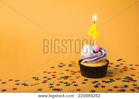 Fourth Birthday Cupcake With Candle And Sprinkles On Yellow Background. Card Mockup, Copy Space. Bir