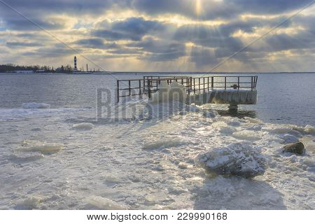 Berth In The Ice Against The Lighthouse At The Mouth Of The River Near The Baltic Sea With Sun Rays