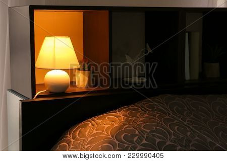 Shelving unit with elegant lamp in room