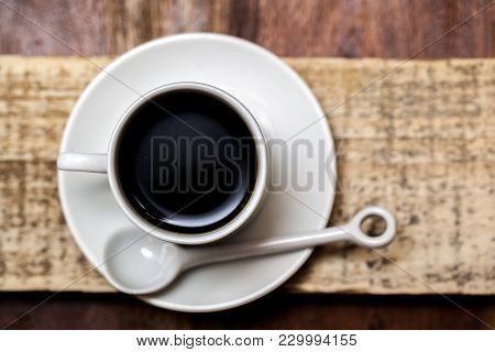 Top View Of Coffee Cup With Spoon And Saucer On A Rustic Wooden Table