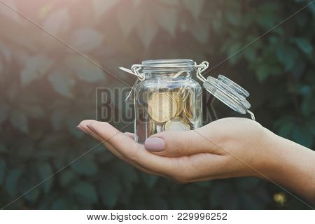 Hand Holding Glass Jar With Coins On Green Leaves Background. Money Saving For House, Dream, Vacatio