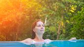 Relaxed woman in blue swimming pool. Girl in open swimming pool. Tropical jungle resort. Summer vacation banner. Ecotourism hotel swimming pool. Exotic holiday. Outdoor swimming pool with natural view poster