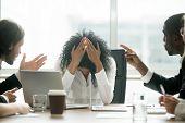 Upset depressed black woman leader suffering from gender discrimination inequality at work, diverse men colleagues pointing fingers scolding bullying frustrated african businesswoman at workplace poster