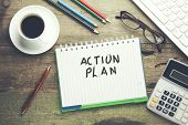 action plan text on notebook with keyboard and stationary on table poster