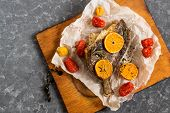 Flounder baked with mandarins and cherry tomatoes. Fish with vegetables and fruits on baking paper and old cutting board poster
