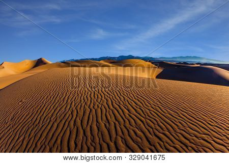 The gentle slopes of the sand dunes are rippled by the wind. Mesquite Flat Sand Dunes is a picturesque part of Death Valley in California. USA. Concept of active, ecological and photo tourism