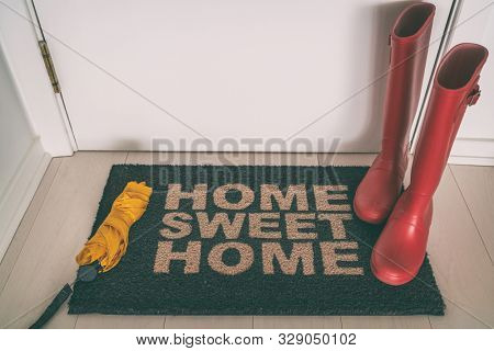Autumn rain boots on entrance door mat at front of house with wet umbrella welcome rug on wooden floor for shoes and winter boots. New house, condo apartment fall winter concept.