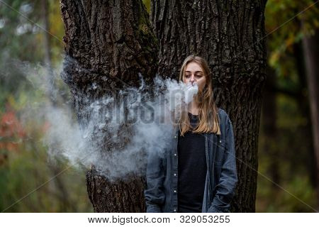 Vape Teenager. Young White Addict Caucasian Teenage Girl With Bruises Under Eyes In Casual Clothes V