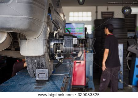 Car Tyre Alignment Wheel Balance At Garage Service Workshop. Mechanic Fixing Car Using Wheel Alignme