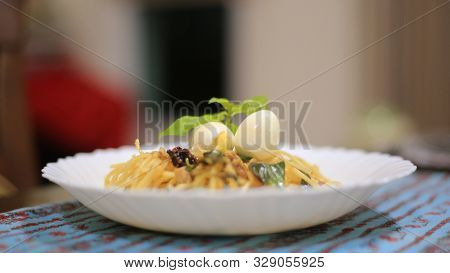 spaghetti anchovy top with boiled quail eggs. fusion Italian food on a local plate mat. poster
