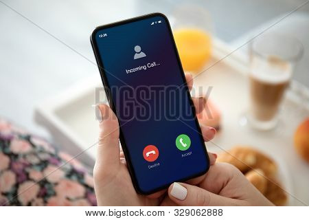 Female Hands Holding Phone With Incoming Call On The Screen In Room