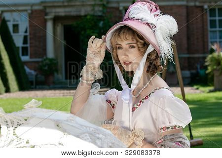 Beautiful Lady In Regency Clothing Sitting On Lawn In Front Of Stately Home Holding Onto Bonnet